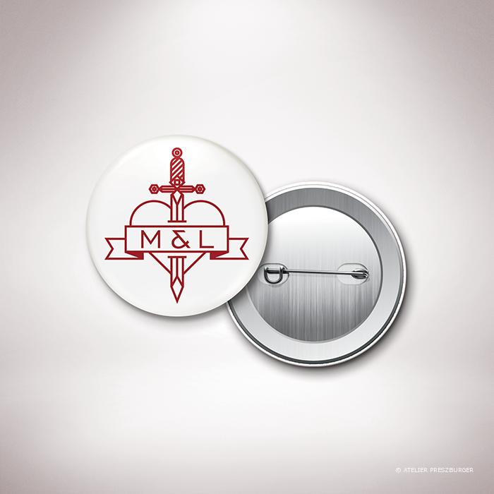 Aumale – Badge de mariage dans un style contemporain sur le thème de l'amour passionné, illustré d'un cœur transpercé d'une dague par Julien Preszburger – Photo non contractuelle